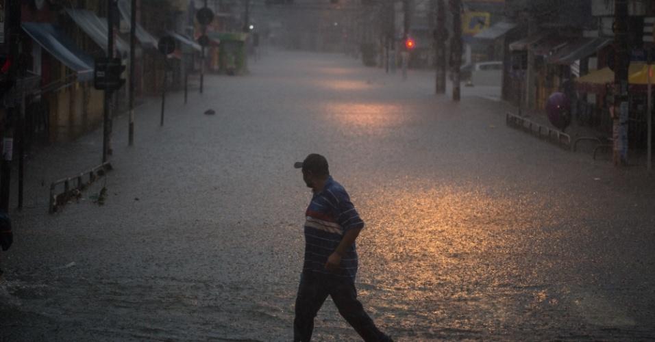 20.mar.2018 - Homem atravessa rua alagada na região da Lapa, zona oeste de São Paulo, após forte temporal