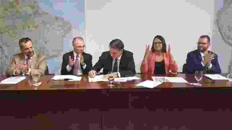 Bolsonaro assina parecer da AGU ao lado de André de Almeida Mendonça, advogado-geral da União - Reprodução/ 25.abr.2019