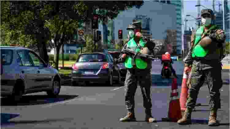 Militares com máscara e armas observam carros passando na rua - Getty Images via BBC - Getty Images via BBC