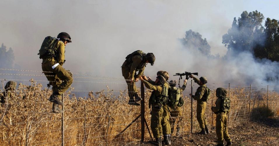 Soldados israelenses fazem vistoria em área atingida por foguete a partir da Síria