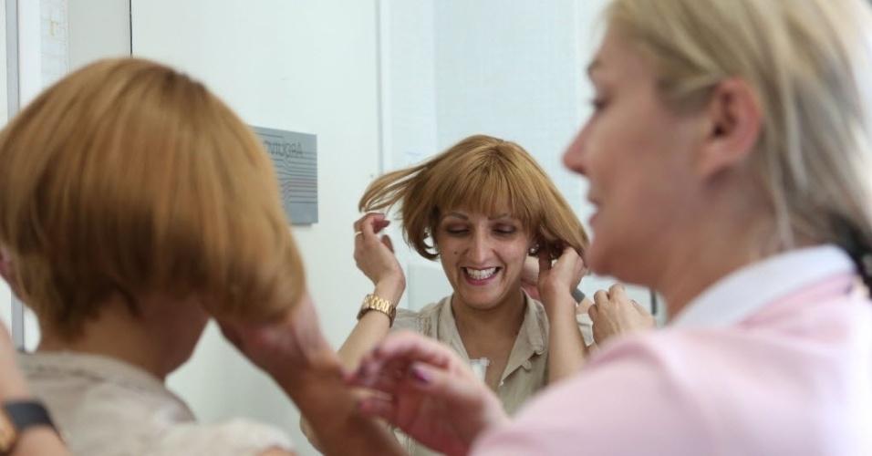 16.out.2015 - A Patrícia é paciente do Instituto do Câncer do Estado de São Paulo (ICESP) e perdeu os cabelos durante o processo da quimioterapia. Com ajuda de voluntárias, Patrícia coloca a peruca que lhe foi dada e sorri ao sentir os novos cabelos. De acordo com o ICESP, 52%  dos pacientes são mulheres, das quais 28% são diagnosticadas com câncer de mama