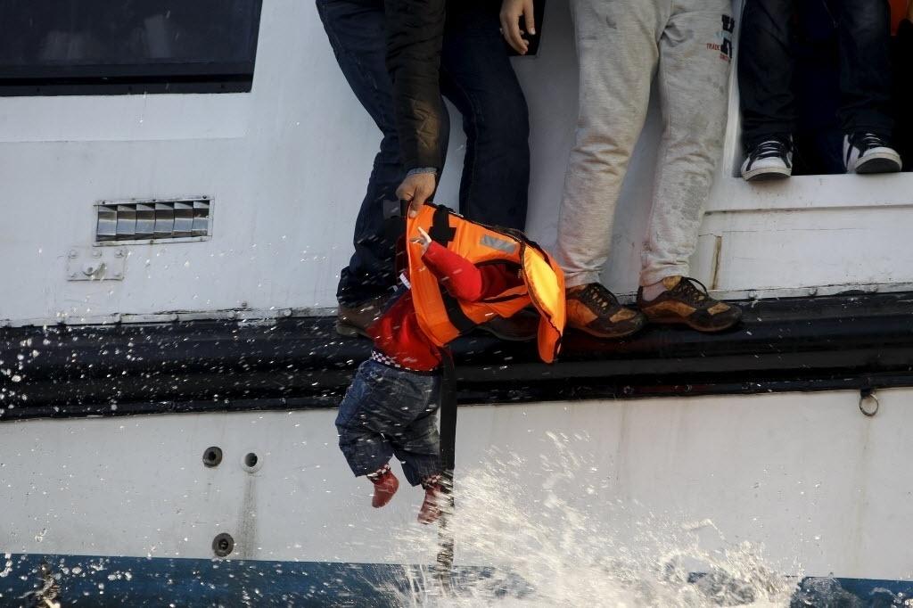 30.out.2015 - Bebê é retirado de barco para ser levado para terra firme na ilha grega de Lesbos. A embarcação em que a criança estava naufragou quando atravessava o mar Egeu, entre a Turquia e a Grécia. O bebê sobreviveu