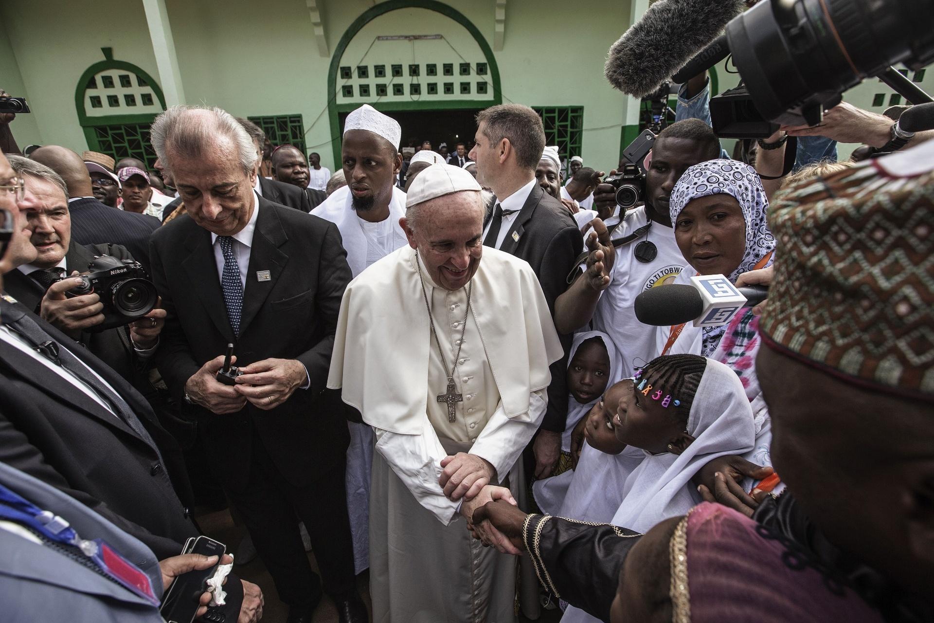 30.nov.2015 - Papa Francisco cumprimenta crianças ao chegar à mesquita central de Bangui, na República Centro-Africana. País imerso em um conflito étnico-religioso que custou a vida de milhares de pessoas nos últimos dois anos, o pontífice afirmou que cristãos e muçulmanos que são