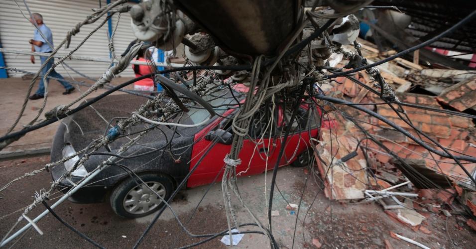 17.abr.2016 - Carro é esmagado por poste na cidade de Portoviejo, Equador, após terremoto de magnitude 7,8 atingir o país na noite de sábado (16). Pelo menos 233 pessoas morreram e mais de 1.500 ficaram feridas. Epicentro do tremor foi a 27 km da cidade de Muisne, perto da fronteira com a Colômbia, a uma profundidade de 19,2 km no oceano Pacífico