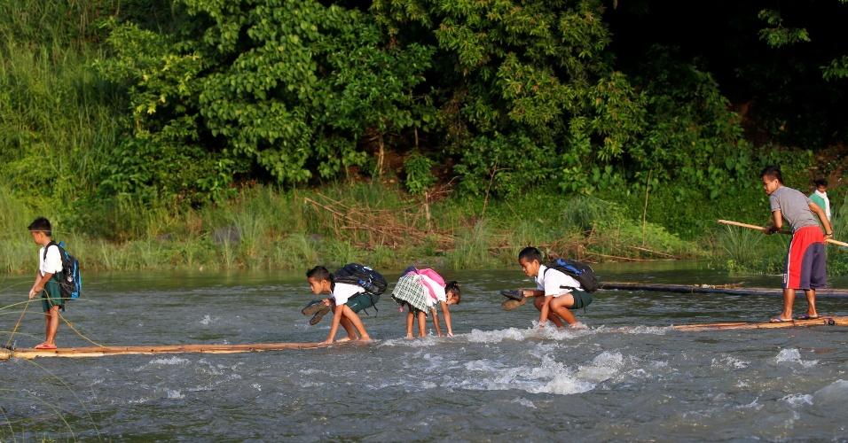 13.jun.2016 - Crianças filipinas improvisam uma pequena balsa para cruzar rio e seguir caminho até a escola em Montalban, ao nordeste da capital Manila
