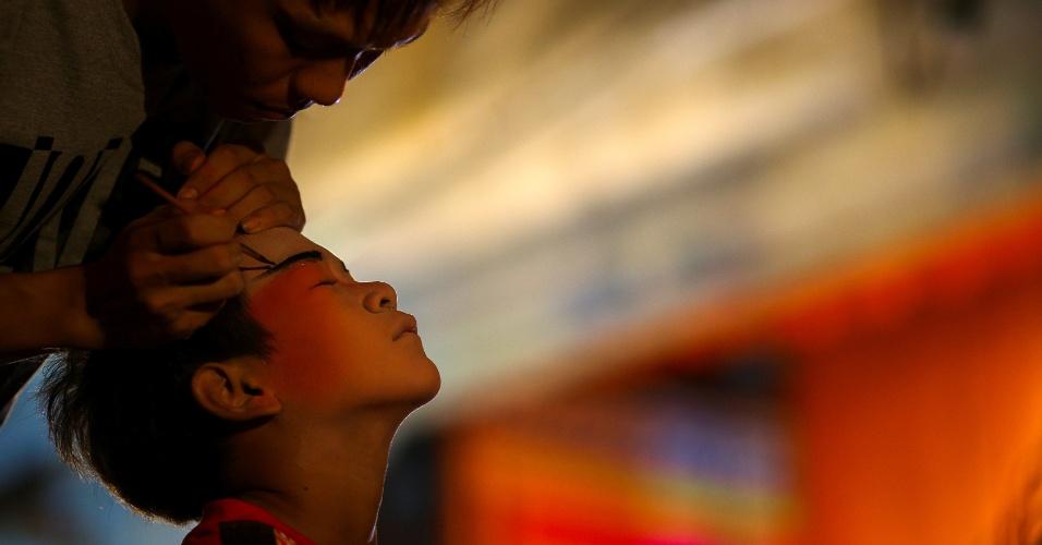 4.out.2016 - Membro da trupe de ópera chinesa aplica maquiagem em criança antes de apresentação em santuário durante o festival vegetariano anual em Bangkok, na Tailândia
