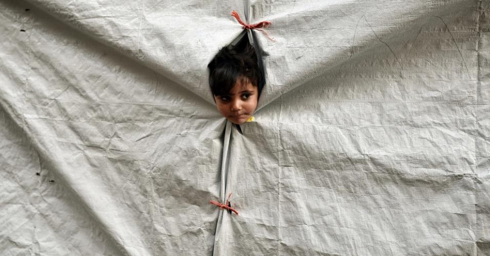 13.out.2016 - Criança espreita para fora de sua barraca no campo de refugiados de Souda, na ilha de Chios (Grécia)