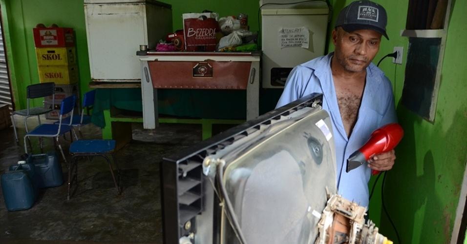 31.mai.2017 - Edvaldo Luiz dos Santos, 47, comerciante, tenta secar uma das duas televisões que perdeu com a enchente em Jacuípe (AL)
