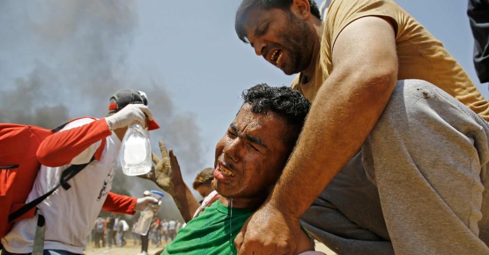 14.mai.2018 - Homem ferido é resgatado durante confronto entre manifestantes palestions e forças israelenses em Jabalia, na Faixa de Gaza