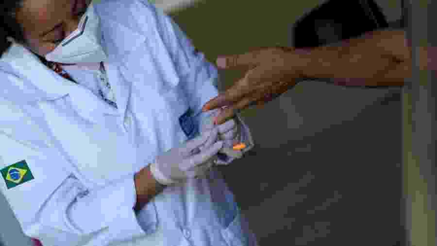 Agente de saúde realiza testa para Covid-19 em motorista de táxi no Rio - Ricardo Moraes