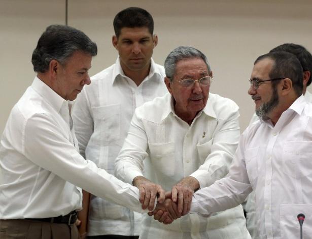 """Mediados pelo presidente de Cuba, Raúl Castro (centro), o presidente da Colômbia, Juan Manuel Santos (esq.), e o líder máximo das Farc, Rodrigo Londoño (dir.), conhecido como """"Timochenko"""", dão aperto de mãos histórico"""