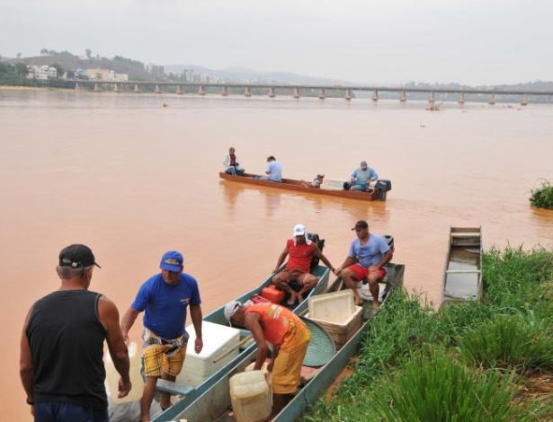 Pescadores tentam retirar peixes do Rio Doce, em Colatina (ES), após a invasão da lama da barragem rompida em Marina (MG)
