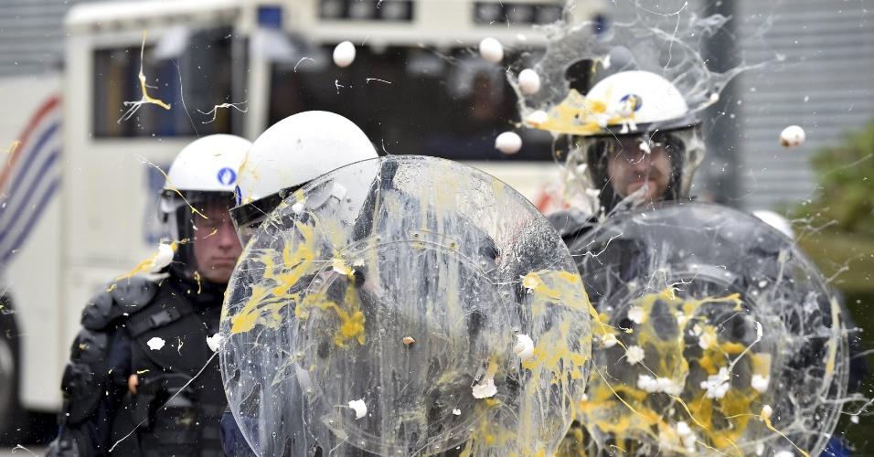 7.set.2015 - Policiais são atingidos por ovos, arremessados por agricultores e produtores de leite de toda a Europa em uma manifestação em frente a reunião de emergência dos ministros da Agricultura da União Europeia na sede de seu Conselho em Bruxelas, na Bélgica