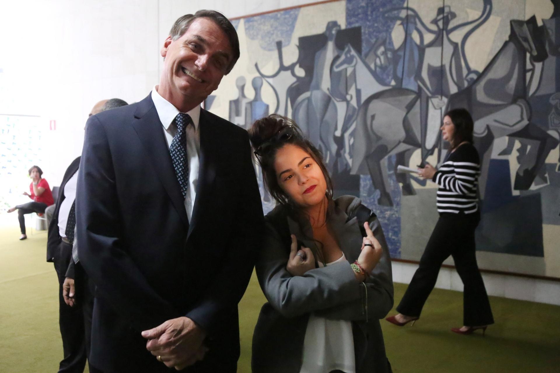 18.mai.2016 - Uma estudante mostra o dedo do meio ao tirar foto com o deputado Jair Bolsonaro (PSC-RJ) no Congresso Nacional, em Brasília. Alunos paulistas que visitaram o local discutiram com o deputado ao conversar sobre sexualidade no salão verde. O debate também envolveu temas como militares e drogas