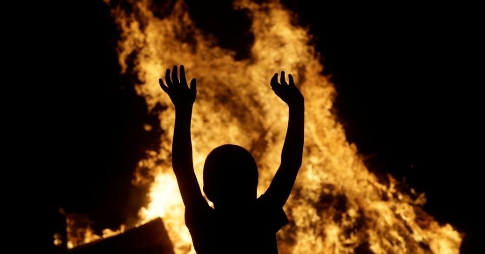 24.jun.2016 - Uma criança brinca na fogueira para comemorar o dia de São João em Paredes, na Espanha