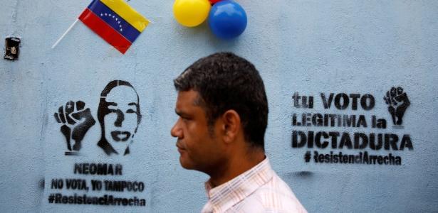 """15.out.2017 - Homem passa diante de grafite onde se lê """"Neomar não vota, nem eu"""" (esq.) e """"Seu voto legitima a ditadura"""", em referência a Neomar Lander, morto durante confrontos com as forças de segurança, em Caracas, Venezuela"""