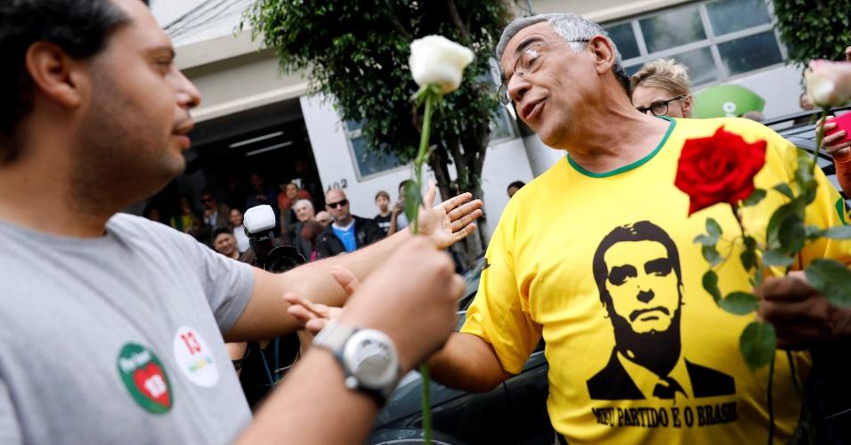28.out.2018 - Um apoiador do candidato Fernando Haddad (PT) entrega uma rosa a um eleitor de Jair Bolsonaro (PSL) durante um segundo turno em São Paulo