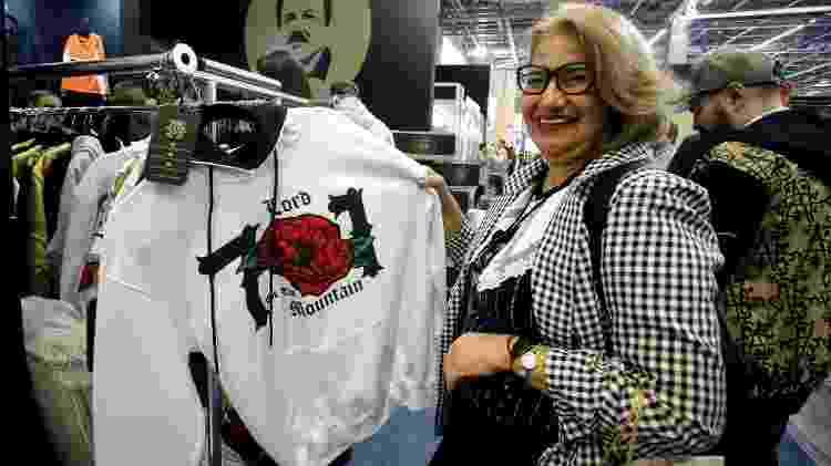 "Mulher sorri enquanto escolhe uma roupa da marca ""El Chapo 701"" - Ulises Ruiz/AFP"
