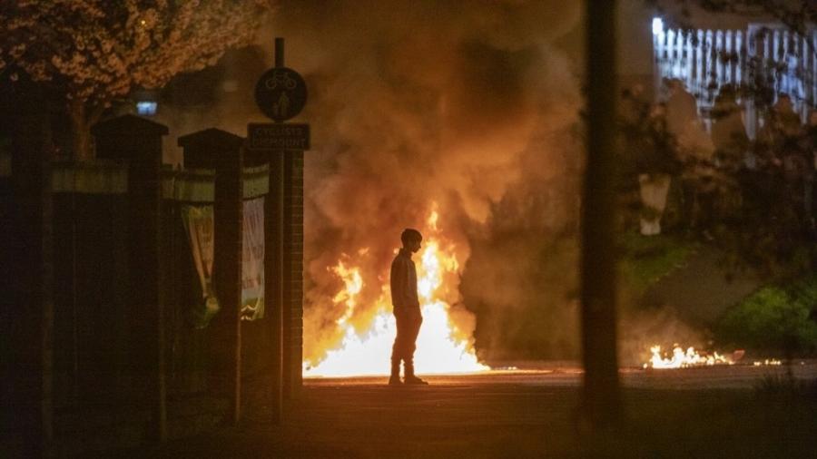 Garoto aparece próximo a chamas durante um distúrbio em Belfast, na Irlanda do Norte - 3.abr.2021 - Paul Faith/AFP