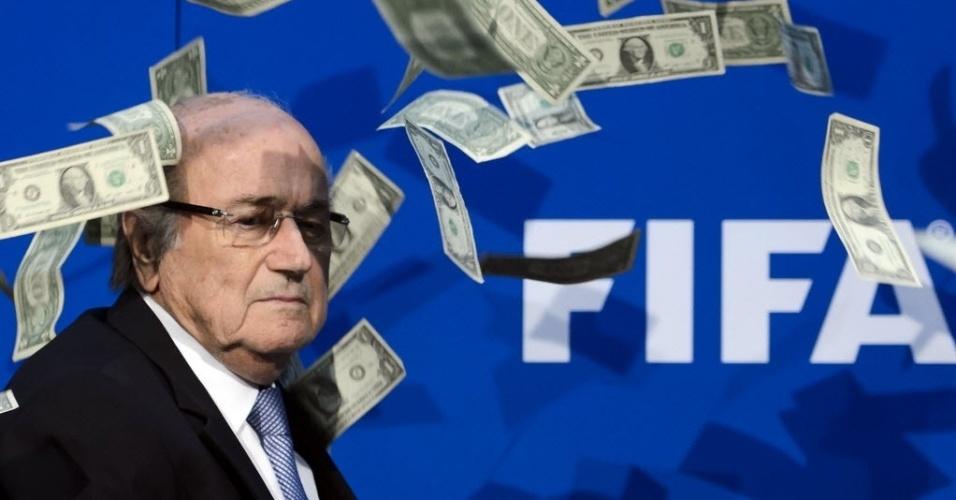 20.jul.2015 - Dólares de mentira jogados por um manifestante que protestava contra a corrupção caem sobre o presidente da Fifa, Joseph Blatter, durante uma conferência com jornalistas em Zurique, na Suíça. Uma eleição especial será realizada em 26 de fevereiro de 2016 para substituir Blatter