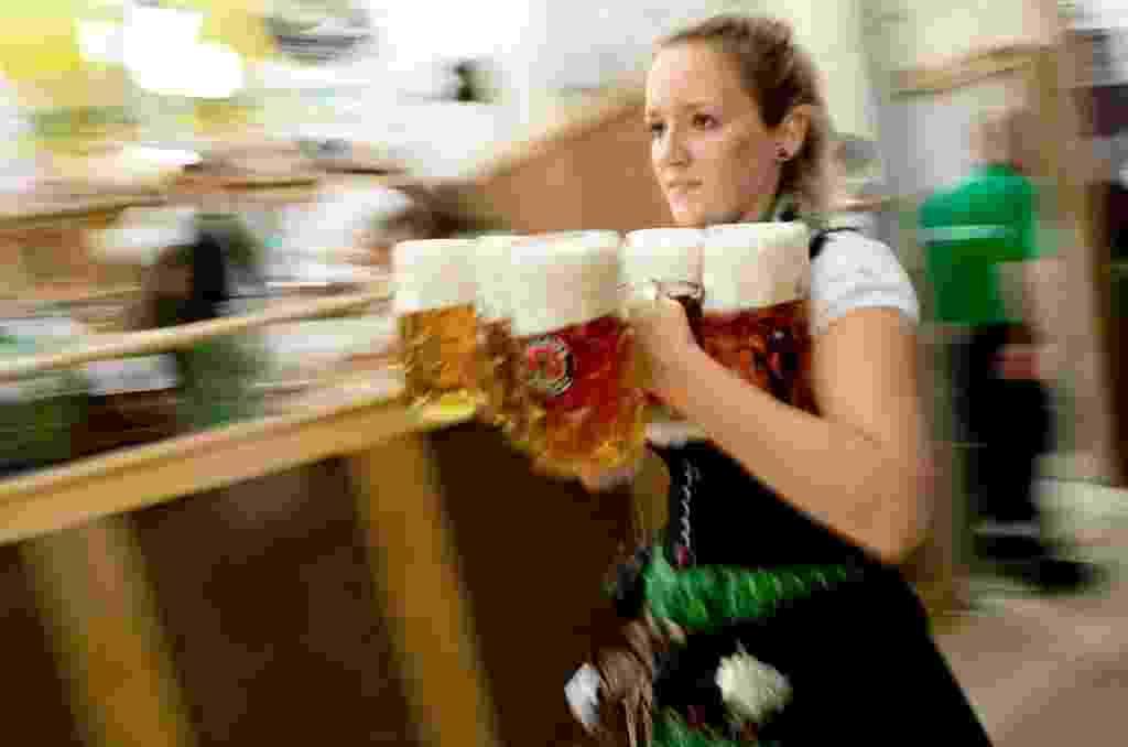 19.set.2015 - Garçonete corre com canecas de cerveja para servir os visitantes da 182ª Oktoberfes, em Munique, na Alemanha. Até o dia 4 de outubro, cerca de 6 milhões de pessoas devem participar do maior festival de cerveja do mundo - Sven Hoppe/EFE
