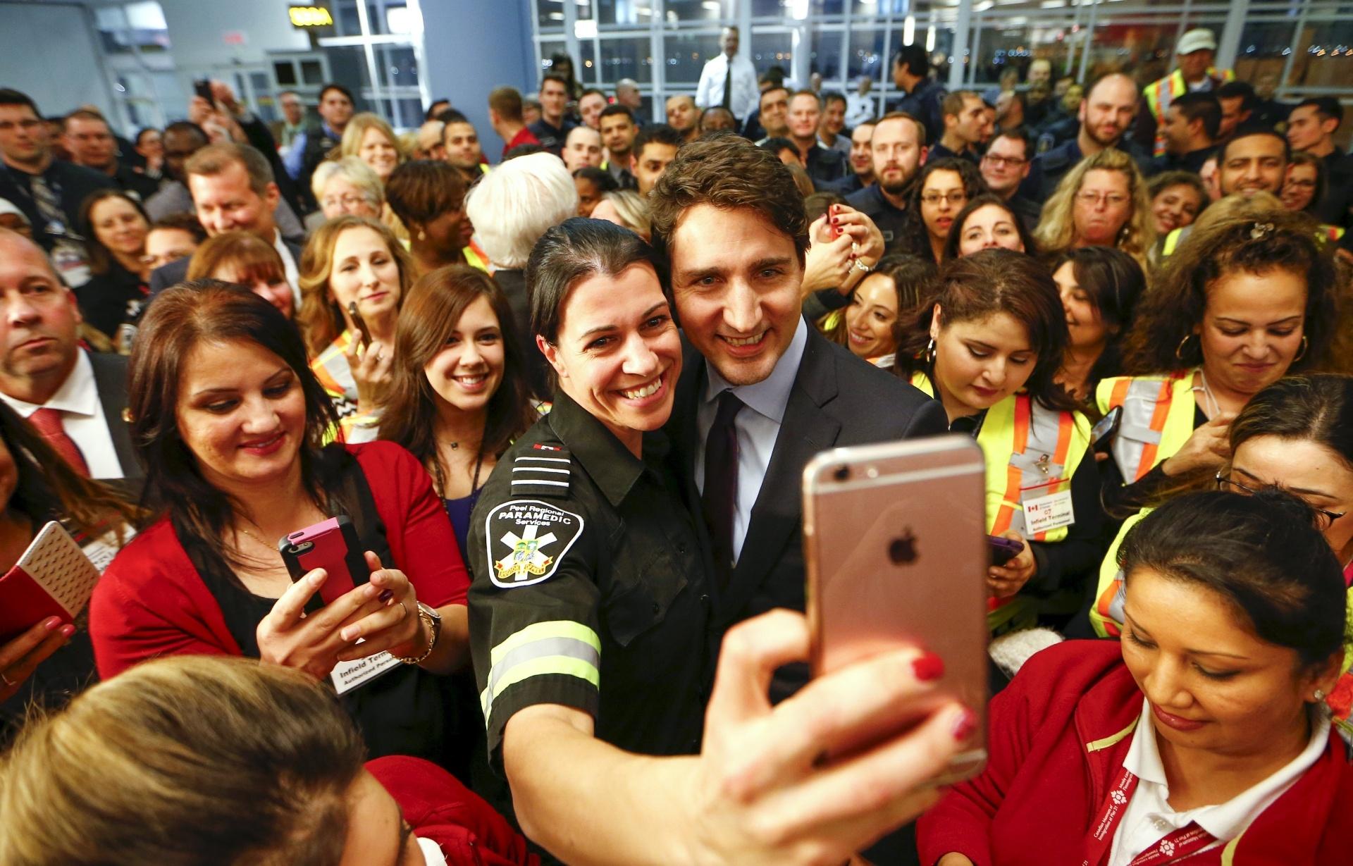 11.dez.2015 - O primeiro-ministro do Canadá, Justin Trudeau, posa para fotos com funcionários do Toronto Pearson International Airport, na região metropolitana de Toronto, em Ontário, enquanto espera pela chegada de refugiados sírios nesta quinta-feira (10). Depois de meses de promessas e semanas de preparação, o premiê vai receber no local o primeiro avião transportando refugiados da Síria