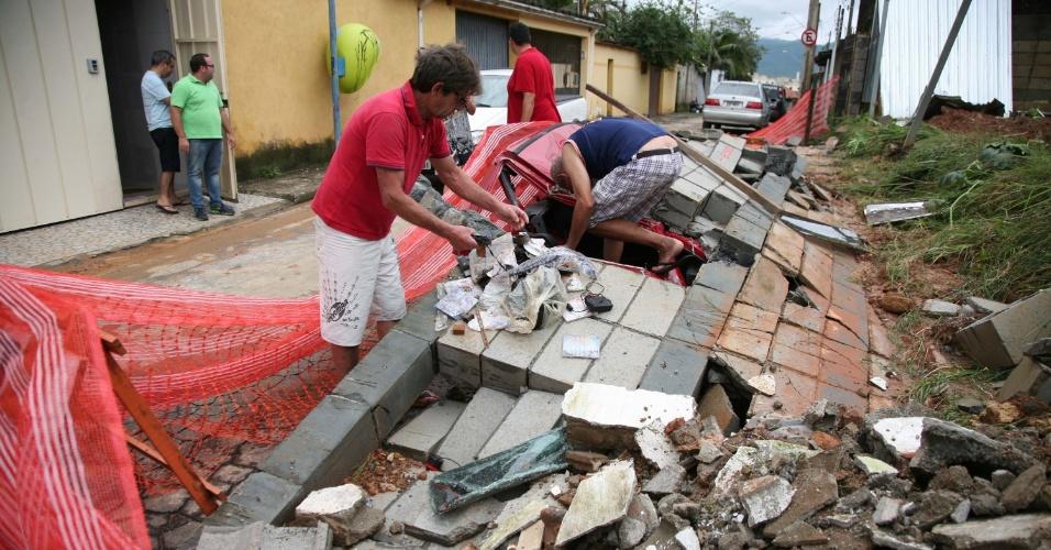2.jan.2016 - Populares retiram escombros de automóvel destruído por muro de obra em construção, em Mogi das Cruzes (SP)