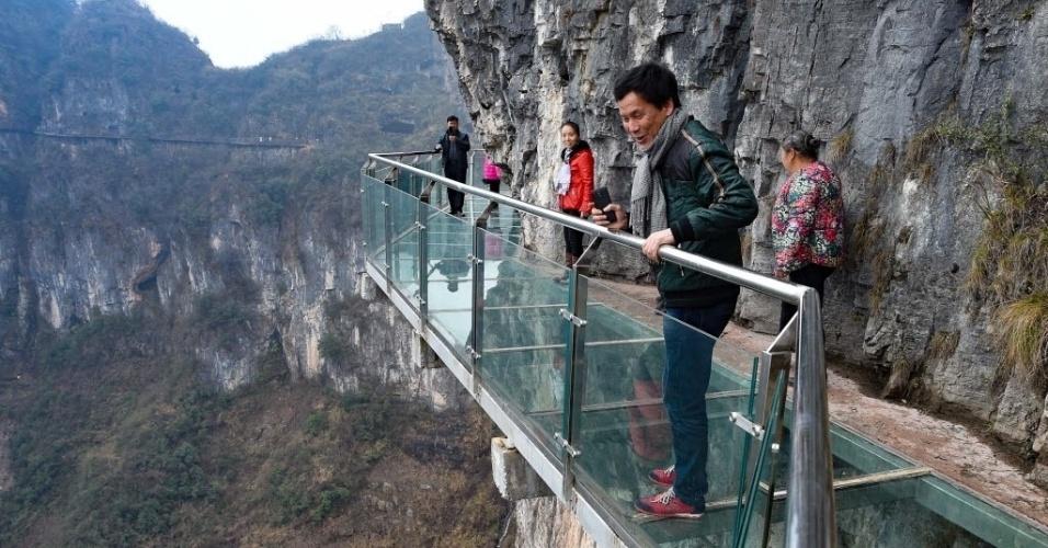 24.fev.2016 - Turistas caminham por uma passarela de vidro no Parque Nacional de Tongren City, na província de Guizhou, na China. A ponte tem 1.005 metros de comprimento, 1,6 metros de largura, e está a mais de 100 metros acima do vale