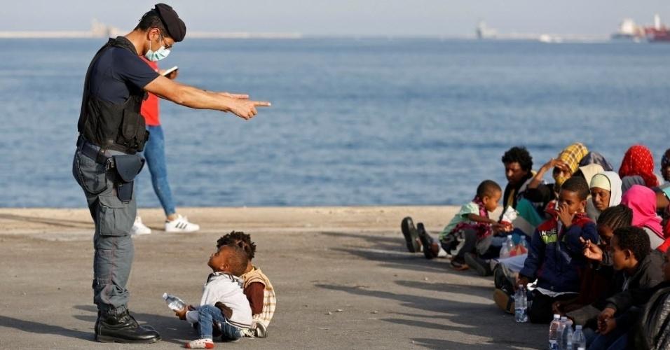 30.jun.2016 - Policial conversar com crianças enquanto imigrantes desembarcam de um navio de socorro que atracou no porto de Augusta, na Itália