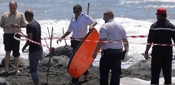 Policial retira prancha de bodyboard de vítima que morreu por ataque de tubarão - Rhicard Bouhet/ AFP
