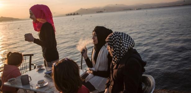 Naram Sebah, uma refugiada síria, fuma com seus amigos no campo de refugiados Skaramagas, em Atenas, Grécia
