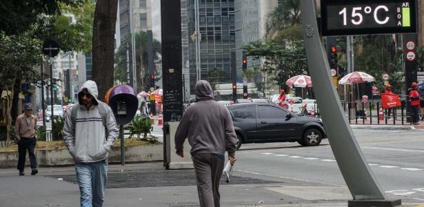 2.ju.2017 - Pedestres caminham se protegendo do frio na avenida Paulista, neste domingo (2)