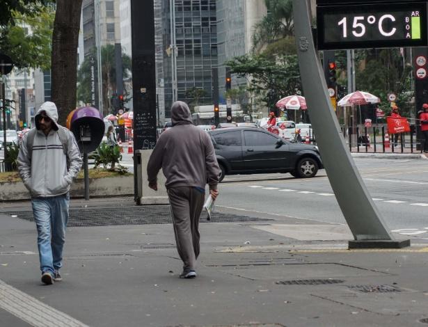 Pedestres caminham se protegendo do frio na avenida Paulista, neste domingo (2)