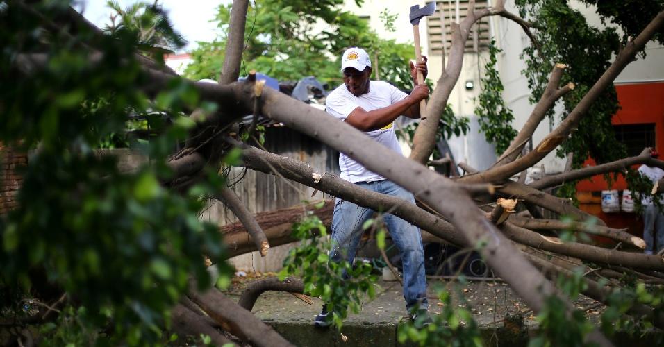 8.set.2017 - Homem tenta cortar galhos de árvores caídas em Puerto Plata, na República Dominicana. A região foi bastante danificada com a passagem do furacão Irma