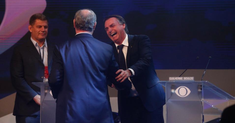9.ago.2018 - Ciro Gomes cumprimenta Jair Bolsonaro com gargalhadas do deputado durante debate da Band