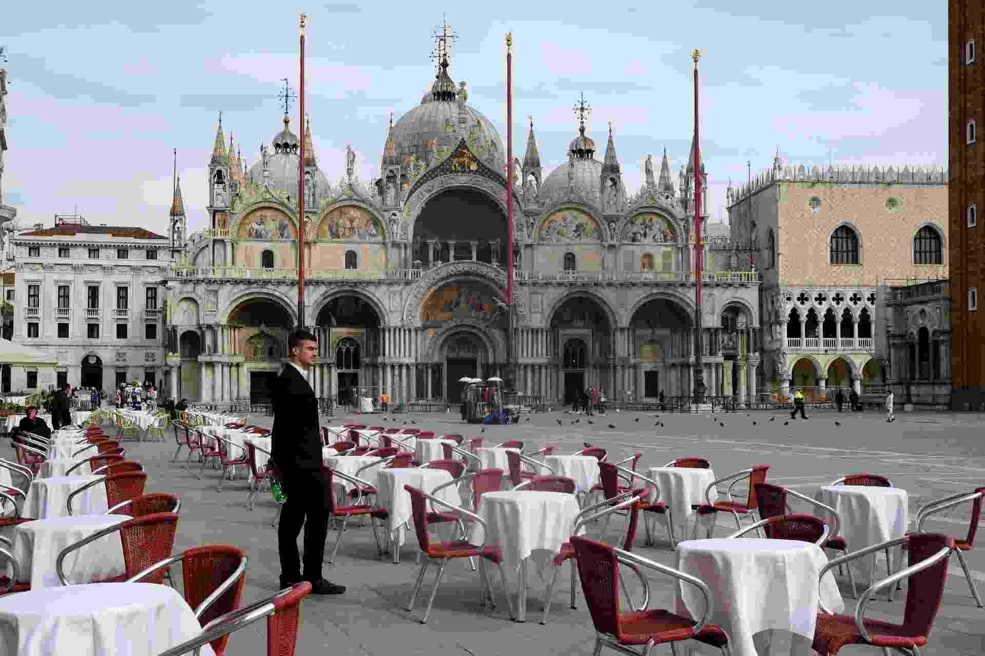 Garçom contempla falta de movimento em restaurante na Praça de São Marcos, em Veneza, frente ao número de contágios de covid-19, doença causada pelo novo coronavírus, na Itália - Manuel Silvestri/Reuters
