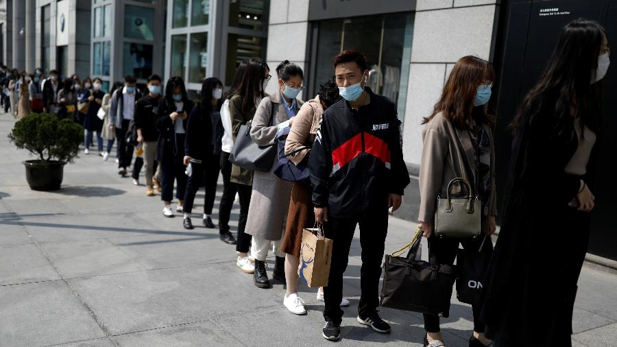 Pessoas usam máscara por causa do coronavírus para entrar em edifício empresarial em Pequim, na China - Carlos Garcia Rawlins/Reuters