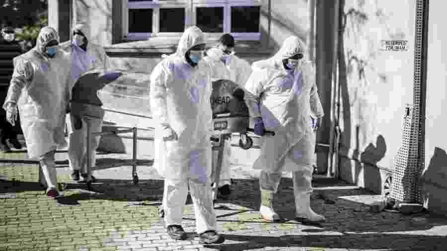 16.jun.2020 - Agentes funerários carregam caixão com corpo de vítima do novo coronavírus, na Cidade do Cabo, na África do Sul - Marco Longari/AFP