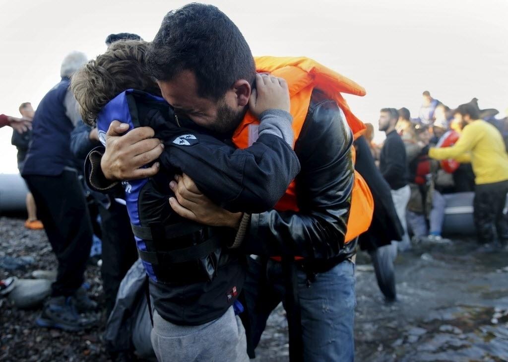 19.nov.2015 - Refugiado sírio abraça o filho após desembarcar na na ilha grega de Lesbos. chanceler da Áustria Werner Faymann, pediu que não haja uma tentativa de vincular refugiados e terroristas, pois os primeiros são