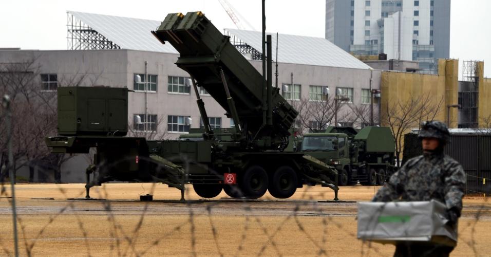 30.jan.2016 - Soldado japonês carrega pacote ao lado de um lançador de mísseis PAC-3 em posição no pátio do Ministério da Defesa, em Tóquio. Nesta sexta-feira, o Japão ordenou a seus militares que estejam de prontidão para destruir qualquer míssil disparado pela Coreia do Norte. O governo japonês suspeita que Pyongyang esteja preparando o lançamento de um foguete