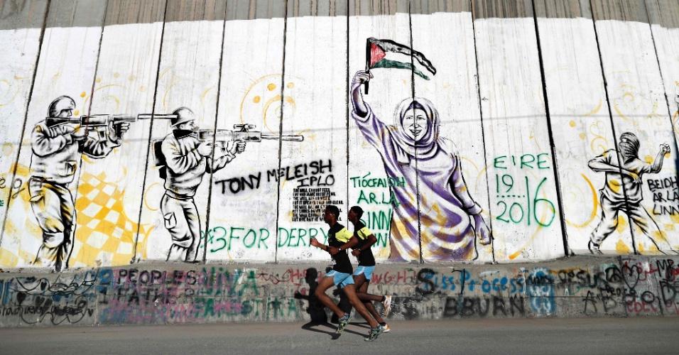 1º.abr.2016 - Participantes correm ao lado da muralha israelense que divide a cidade de Belém, na Cisjordânia ocupada, durante a 4ª maratona da Palestina
