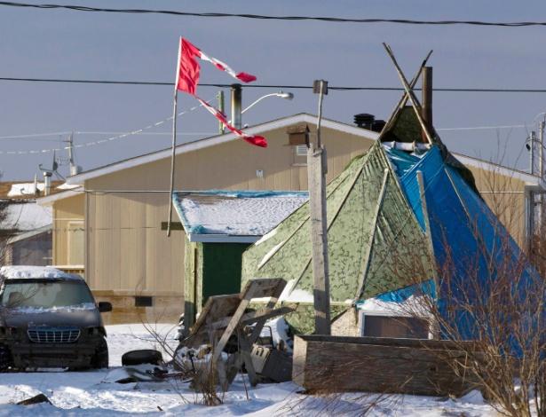 Bandeira canadense esfarrapada tremula sobre uma tenda em Attawapiskat, Ontario