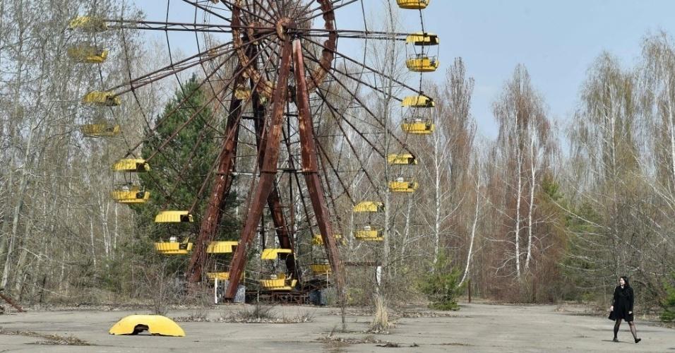 18.abr.2016 - Mulher passa ao lado de roda gigante na cidade fantasma de Prypyat, próxima à usina nuclear de Chernobyl, na Ucrânia. O país se prepara para rememorar o desastre de vazamento radioativo da usina, que completa 30 anos. O reator da usina explodiu com mais de 200 toneladas de urânio em seu interior. O número de mortos do acidente nuclear continua a ser um mistério. A radioatividade ainda coloca em risco a saúde da população local