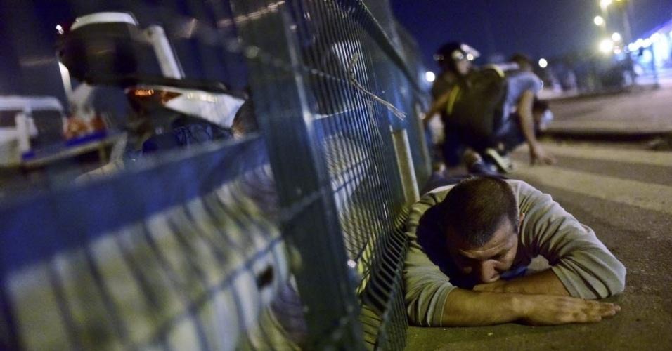 15.jul.2016 - Homens se escondem tentando evitar os tiros em Istambul após tentativa de golpe militar na Turquia. A população foi às ruas e houve confrontos com os militares, motivando uma onda de violência que já deixou policiais e civis mortos. Há relatos de feridos, alguns em estado grave