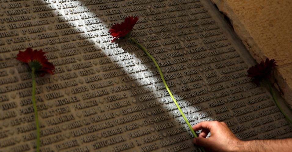 11.set.2016 - Homem coloca flor no monumento onde estão gravados os nomes das vítimas dos ataques de 11 de setembro de 2001, no 15º aniversário dos ataques de Nova York, Virgínia e Pensilvânia