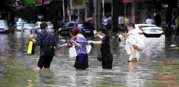23.ago.2017 - Mulheres caminham em rua alagada na cidade de Dongguan, atingida pelo tufão - Reuters - Reuters