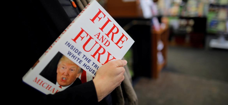 """5.jan.2018 - Mulher leva um exemplar do livro """"Fire and Fury: Inside the Trump White House"""", de Michael Wolff, em uma loja em Washington DC - Carlos Barria/ Reuters"""