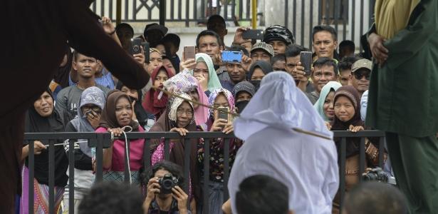Tjia Nyuk Hwa recebe açoite durante castigo público em frente a mesquita em Aceh, na Indonésia