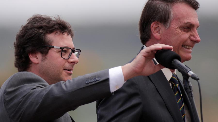 Chefe da Secom, Fabio Wajngarten, arruma microfone ao lado do presidente Jair Bolsonaro no Palácio da Alvorada - Reprodução