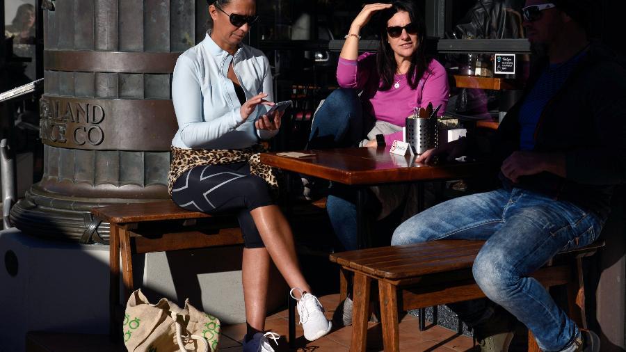 Clientes de café na Nova Zelândia conversam na área externa após suspensão total de restrições - STRINGER
